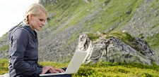 student with laptop out on hillside