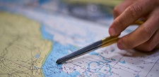 A hand pointing on a map with a pen