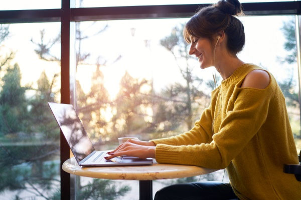 Woman at desk with laptop, large window behind