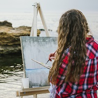 Girl with easel by the sea