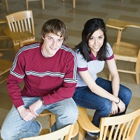 Male and female student surrounded by empty chairs