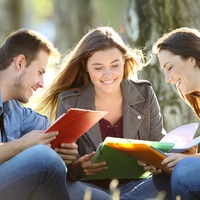 Mixed group of three students with books, talking
