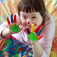 Child with multicoloured paint on hands