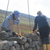 Two people building a stone wall